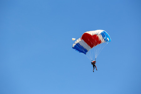 isolated skydiver  control colorful parachute gliding after free fall jump with blue sky background  and copy space Imagens - 106384707