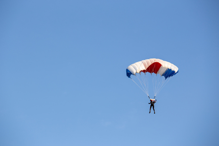 isolated skydiver  control colorful parachute gliding after free fall jump with blue sky background  and copy space Imagens - 106384723