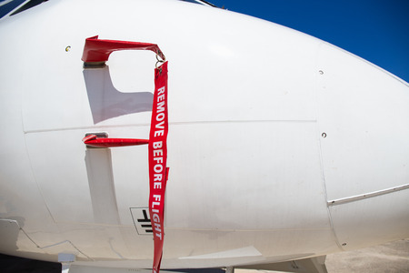 remove before flight flag cover pitot static tube of white aircraft at parking area in airport