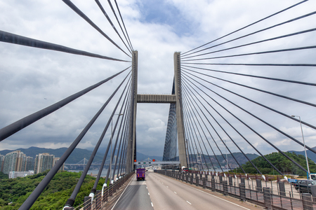 Tsing Ma double-decked suspension bridge between Ma Wan island and Tsing Yi island in Hong Kong, China by road view with sky background and copy space 版權商用圖片