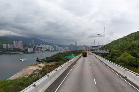 Tsing Yi North Coastal Road in Tsing Yi island connect to New Territories in Hong Kong from double decker bus view with sea mountain rang and city background with copy space