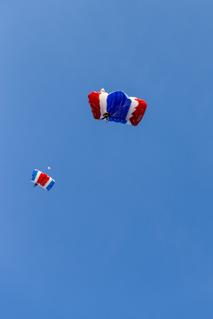 skydiver team in colorful parachute gliding after free fall jump with blue sky background  and copy space Stok Fotoğraf