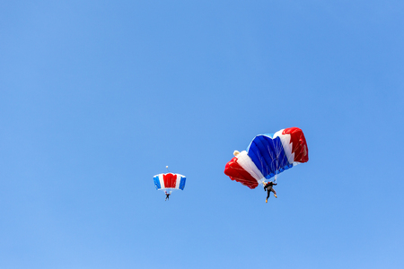 skydiver team in colorful parachute gliding after free fall jump with blue sky background  and copy space Imagens