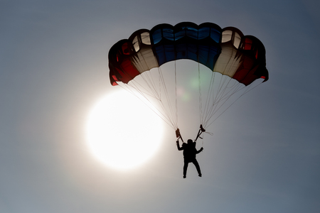 silhouette isolated skydiver gliding after free fall jump with sun background and copy space Imagens