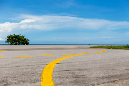 yellow line on taxiway lead to runway at airfield with sea and blue sky background