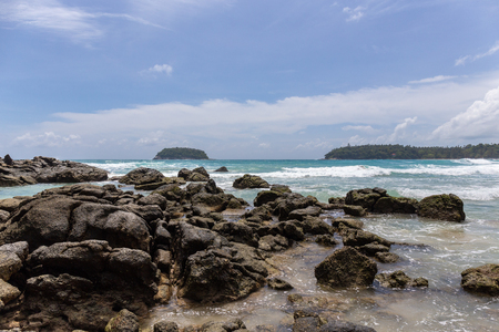 rock and clear sea water with blue sky background in summer season at Kata beach, Phuket island of Thailand