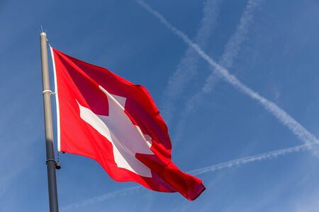 switzerland flag waving with crossing flight trail on blue sky background in summer day and copy space Imagens - 141663174