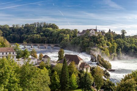 Rheinfall the large and powerful waterfall surround with green forest and blue sky background view from Neuhausen am Rheinfall railway station in switzerlad