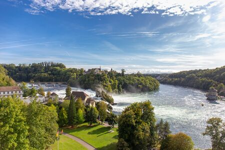 Rheinfall the large and powerful waterfall surround with green forest and blue sky background view from Neuhausen am Rheinfall railway station in switzerlad Imagens - 143676492