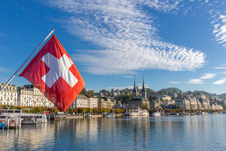LUCERNE, SWITZERLAND - OCTOBER 1, 2019 - Swiss flag and landscape of Luzern and  Reuss river with historical building and blue sky background. Lucerne is the most populous town in Central Switzerland. Imagens - 142095978