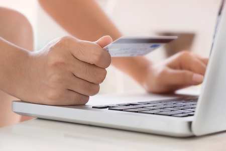 e card: Woman hold Credit Card on laptop waiting for online shopping Stock Photo