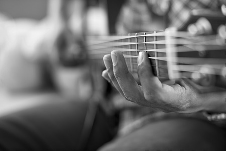 chord: playing acoustic guitar, barre chord,selective focus,black and white tone. Stock Photo