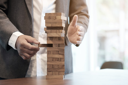 instability:   Planning, risk and strategy in business, businessman gambling placing wooden block on a tower with vintage tone and Risk management and insurance concept, leadership has solution for problem.  Stock Photo