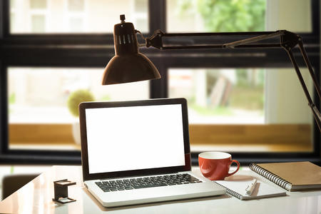 notebook or laptop,red cup,pen,notepad on wood desk against the window with lamp in the morning. Stock Photo