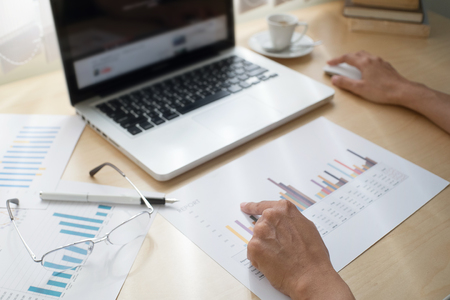 denoting: Business adviser analyzing financial figures denoting the progress in the work of the company with laptop chart board and tablet team of business, selective focus and soft focus. Stock Photo