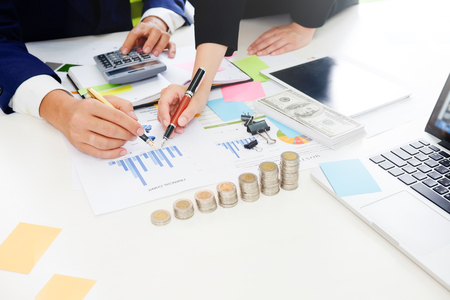 information analysis: Business adviser analyzing financial,Financial planning Business man and Business woman talking to planner financial business, report finance in paper on office accounting. Stock Photo