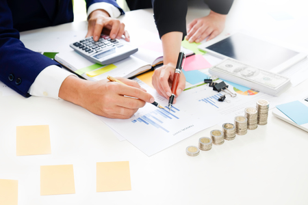 Business adviser analyzing financial,Financial planning Business man and Business woman talking to planner financial business, report finance in paper on office accounting. Stock Photo