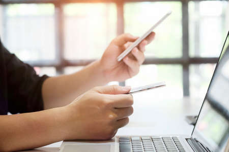 electronic commerce: Hands holding credit card and entering security code using smart phone online shopping concept.