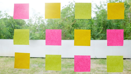 real post it notes to share idea and brainstorming concept on glass windows. Stock Photo