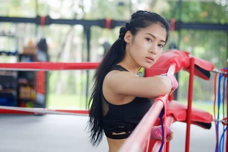 Portrait asian woman on ringside boxing gym.