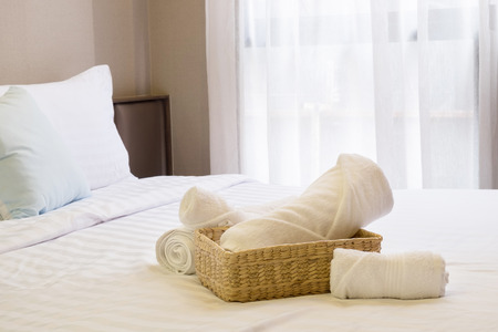 White towel in basket on bed decoration in bedroom.