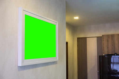 Decorative photo frame on wall with green screen empty a frame. Stock Photo