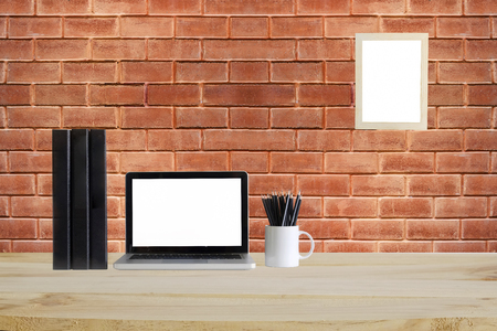 Laptop computer ,file folder document, pencil and photo frame on workspace with wood table and brick wall on background,Mockup concept.