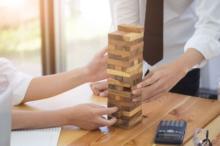 Architectural project concept,engineering playing a blocks wood tower game on blueprint or planning architectural project in engineer, office. Stock Photo