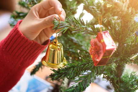 Closeup woman hands decoration a bell on christmas tree,christmas event concept. Stock Photo