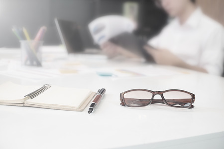 Close up of eye glasses and pen on work desk with chart and laptop at business workplace. Vintage tone. Stock Photo