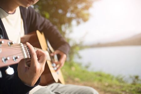 Guitar list on hands with outdoor and nature view.