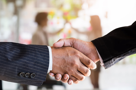 Closeup businessman shaking hands finishing up a meeting,acquisition concept.