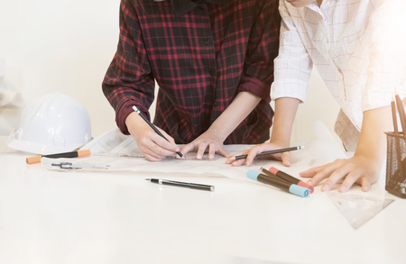architectural drawing concept, two people young business draw a pencil on blue print.