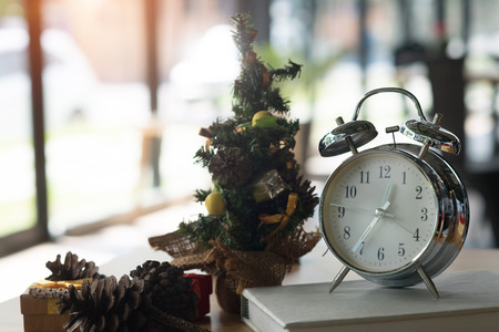 time of Christmas concept,little Christmas tree and decoration event with clock time on desk.