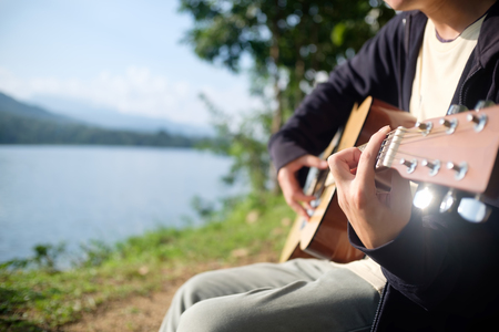 Guitar player play a music on holiday with mountain and lake in camping.