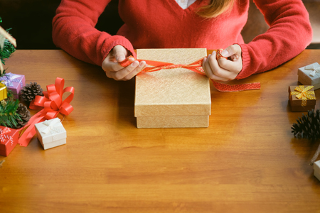 woman holding Christmas presents laid and close gift box on a wooden table background.
