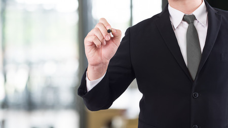 Business writing something or pointing with pen. Stock Photo