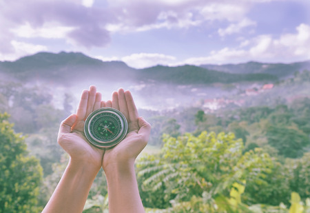 Compass on hands fine a way on nature mountain view with vintage tone. Stock Photo