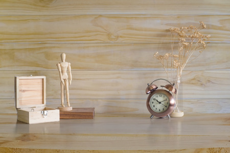Copyspace alarm and decoration on wooden table and wood wall with present or mockup.