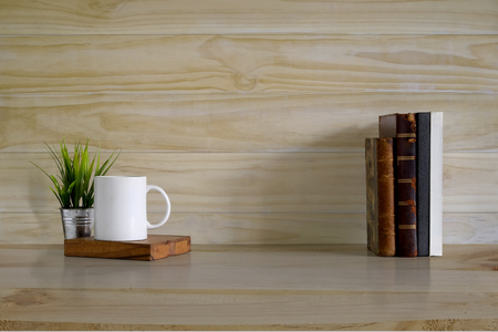 Mockup background, books and coffee mug on wood desk and wooden wall with copy space.