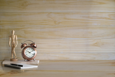 Alarm and decoration on wooden table and wood wall with present or mockup. Stock Photo