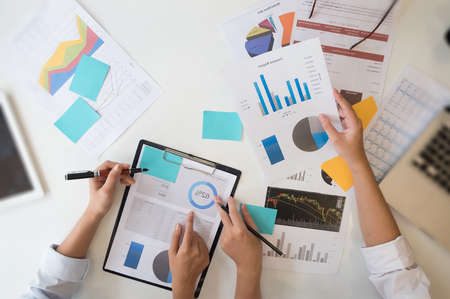Business meeting concept, top view people working with paper data chart document on office business table.
