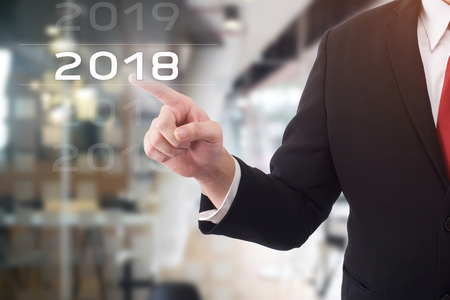 Businessman pointing year 2018 welcome year 2018. Business new year card concept