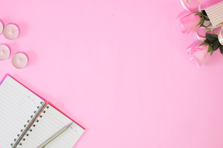Notebook and pen with pink rose flower on pink table copy space top view. Stock Photo