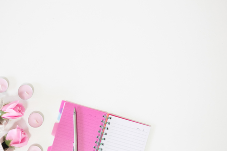 Notebook and pen with rose flower on table copy space top view. Stock Photo