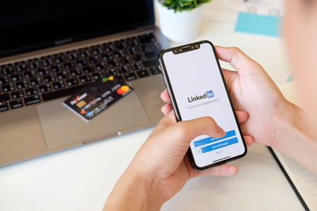 CHIANGMAI,THAILAND 22 FEB 2018 : Man holding New iPhone X on hand open LinkedIn application on the screen. LinkedIn is a business-oriented social networking service. Editorial
