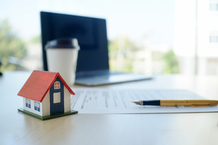 house contract Mortgage contract for sale of real estate property with a pen and house model.