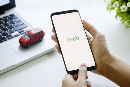 CHIANG MAI,THAILAND - FEB 19, 2018 : Samsung galaxy S8 Plus open grab application on woman hands,Grab taxi Many Thailand people are attracted to join the ride sharing services business.