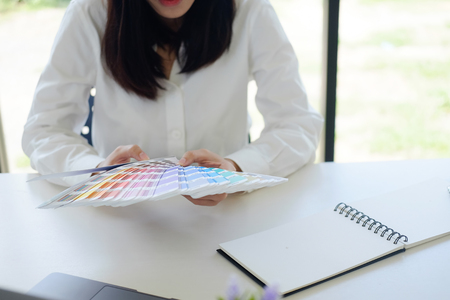Female working creative designer job she select and planning colour project.
