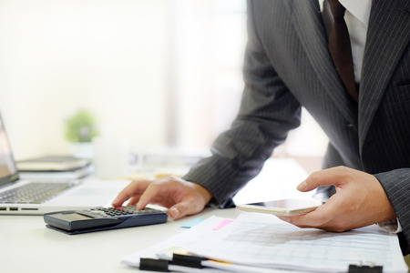 Certified public accountant, Man working on smartphone tablet computer and spreadsheet document financial data.